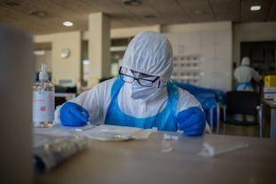 Un voluntario de la ONG Proactiva Open Arms deposita en una placa de test rápido la sangre que ha extraído a un trabajador sanitario de una residencia.