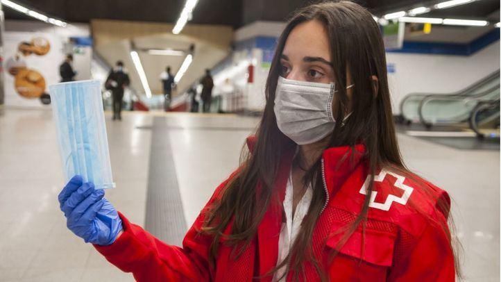 Voluntarios de la Cruz Roja reparten mascarillas en el Metro.