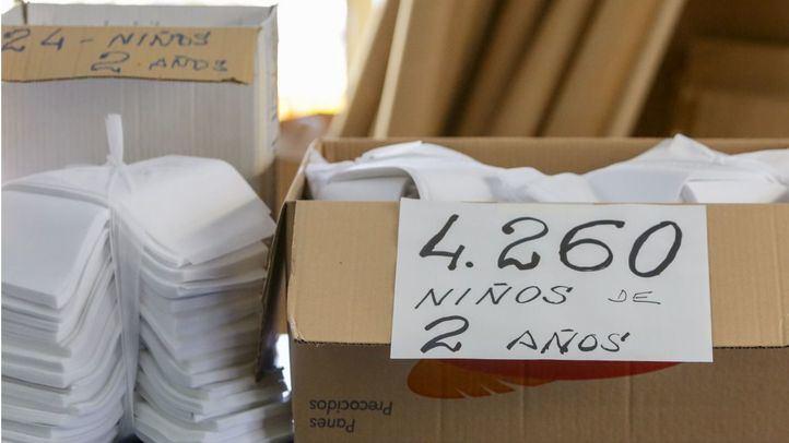 Caja con telas para fabricar mascarillas para niños que han cortado voluntarios vecinos de La Cabrera.
