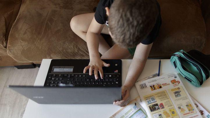 Un alumno de primaria hace los deberes con varios libros y un ordenador a menos de un mes de terminar en casa el curso escolar 2019-2020 por la pandemia del Covid-19.