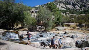 Senderistas saltan las rocas para llegar a a la Charca Verde, en La Pedriza.