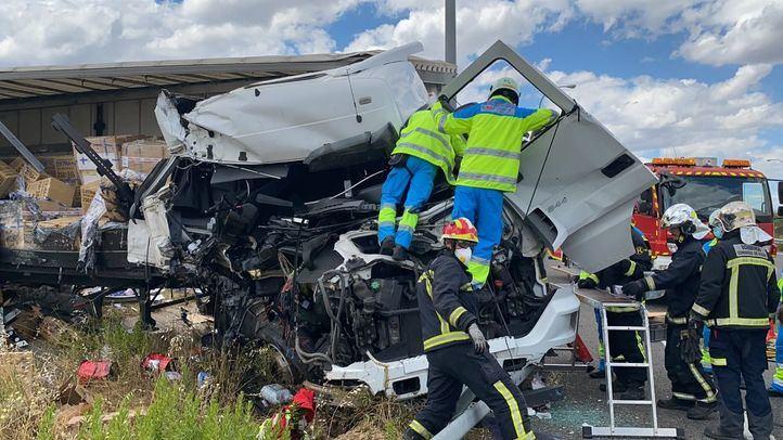 Bomberos y el personal sanitario tratan de rescatar a uno de los camioneros involucrados en el accidente.