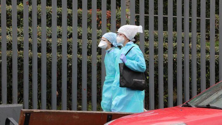 Dos trabajadoras protegidas pasean al lado de una residencia. [Imagen de archivo]