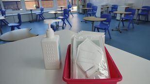 Mascarillas y gel desinfectante en la mesa del profesor de un aula.