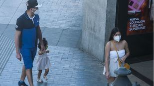Dos adultos utilizan la mascarilla por el centro de Madrid