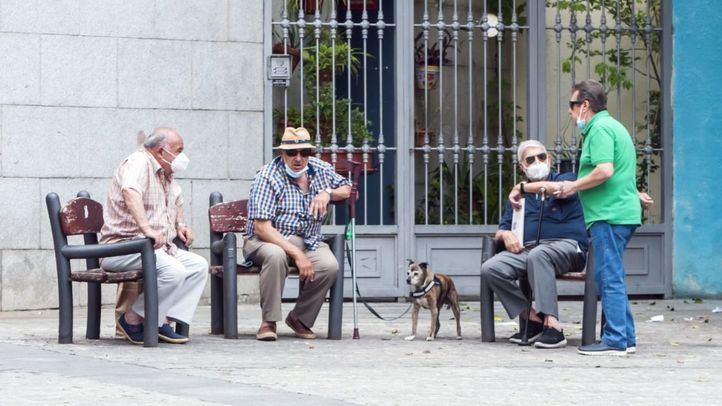 Un grupo de hombres se reúne frente al Teatro Real