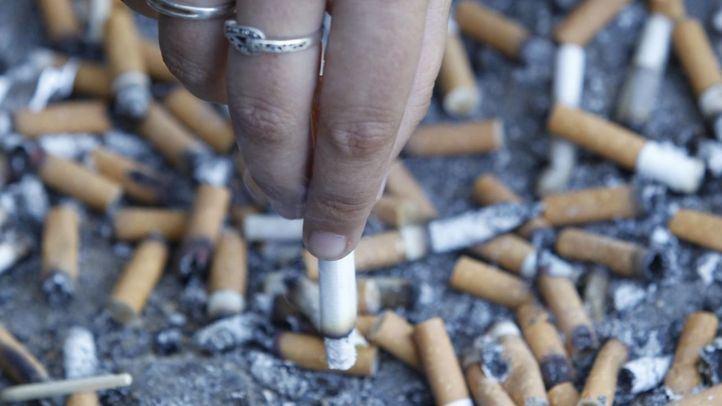 Mujer apagando un cigarro en un cenicero