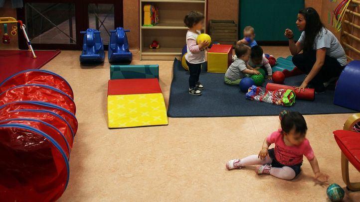 Niños jugando con su cuidadora en una escuela infantil en Delicias, Madrid.