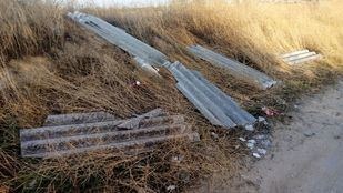 Placas de fibrocemento que contienen amianto, abandonadas en una vía pecuaria