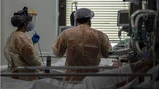 Dos sanitarios atienden a un enfermo con coronavirus en la UCI del Hospital Ramón y Cajal