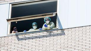 Sanitarios en una ventana del Hospital Gregorio Marañón.