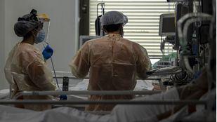 Dos sanitarios atienden a un enfermo con covid en la UCI del Hospital Ramón y Cajal