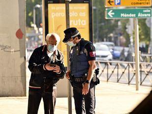 Hombre enseña en Puente de Vallecas un justificante a un agente de la Policía Municipal