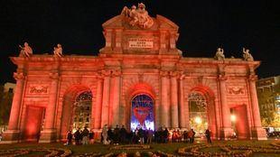 La Puerta de Alcalá en rojo en la víspera del Día Mundial de la Lucha contra el Sida