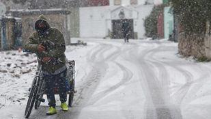Un hombre empuja una bicicleta en la Cañada Real tras la nevada
