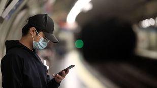 Un joven mira su móvil mientras espera la llegada del metro