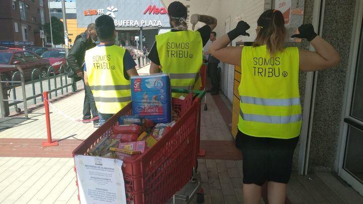 Tres voluntarios de la red de apoyo vecinal colaboran en el reparto de alimentos.