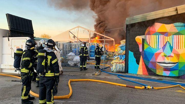 Los bomberos trabajan en la extinción de un aparatoso incendio en una nave