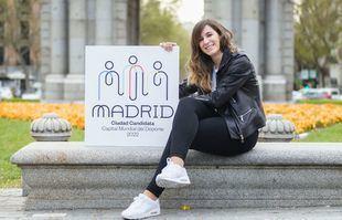 Sofía Miranda, concejala de Deporte de Madrid, junto al logo de la candidatura de la ciudad a Capital Mundial del Deporte 2022.