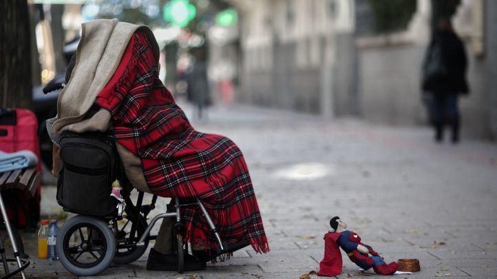 Una persona en silla de ruedas y tapada con una manta pide dinero con un muñeco de Superman en una céntrica calle durante la segunda ola de la pandemia del coronavirus