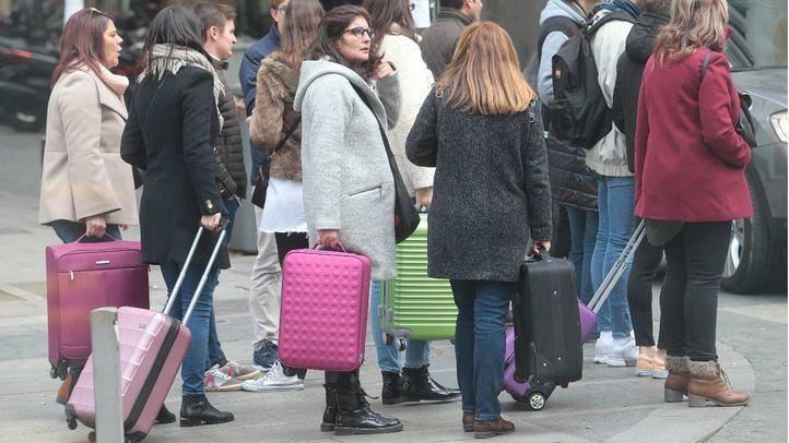 Turistas con maletas, en una foto de archivo
