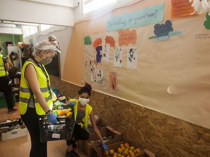 Voluntarios de la asociación Alma Latina preparan cestas de comida.