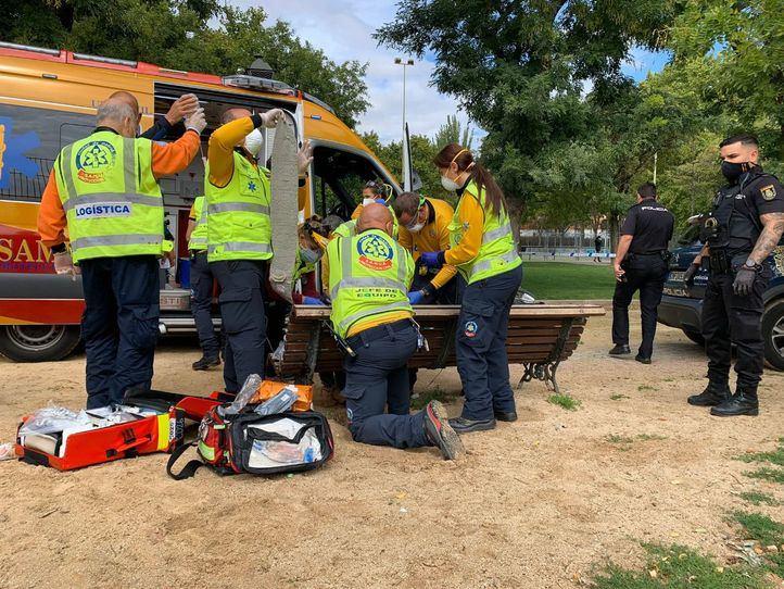Los sanitarios atienden al herido en un banco del parque