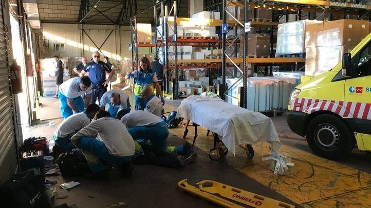 Foto de archivo: sanitarios atendiendo a un hombre herido por un accidente laboral