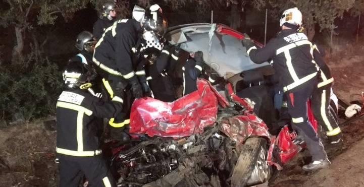 Los bomberos rescatan los cuerpos de los dos fallecidos en el choque frontal